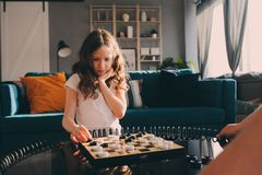 Lifestyle shot of smart kid girl playing checkers at home royalty free stock photo