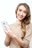 Lifestyle stylish girl using phone texting on smartphone app. Face with toothy smile. Beauty stylish blonde woman with pink lips Stock Photos