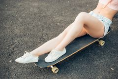Woman with longboard sitting on the ground. Lifestyle, summer and people concept - smiling young woman or teenage girl sitting on longboard on city street Royalty Free Stock Photos