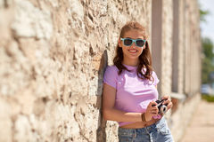 Happy teenage girl in shades with camera on street. Lifestyle, summer and people concept - smiling young woman or teenage girl in sunglasses with camera on city Royalty Free Stock Photo