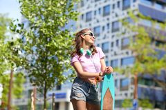Happy teenage girl in shades with longboard. Lifestyle, summer and people concept - smiling young woman or teenage girl in sunglasses with longboard on city Stock Photography