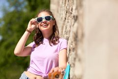 Happy teenage girl in shades with longboard. Lifestyle, summer and people concept - smiling young woman or teenage girl in sunglasses with longboard over stone Royalty Free Stock Photos