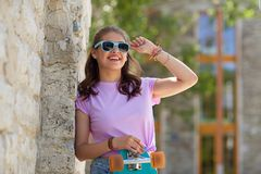 Happy teenage girl in shades with longboard. Lifestyle, summer and people concept - smiling young woman or teenage girl in sunglasses with longboard over stone Stock Images