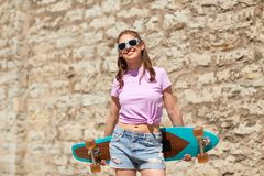 Happy teenage girl in shades with longboard. Lifestyle, summer and people concept - smiling young woman or teenage girl in sunglasses with longboard over stone Stock Photo