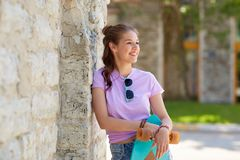 Happy teenage girl in shades with longboard. Lifestyle, summer and people concept - smiling young woman or teenage girl in sunglasses with longboard over stone Stock Image