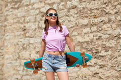 Happy teenage girl in shades with longboard. Lifestyle, summer and people concept - smiling young woman or teenage girl in sunglasses with longboard over stone Royalty Free Stock Images