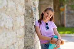 Happy teenage girl in shades with longboard. Lifestyle, summer and people concept - smiling young woman or teenage girl in sunglasses with longboard over stone Stock Photos