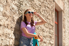 Happy teenage girl in shades with longboard. Lifestyle, summer and people concept - smiling young woman or teenage girl in sunglasses with longboard over stone Royalty Free Stock Image