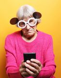 Lifestyle, tehnology and people concept: Elderly lady holding a smartphone stock images