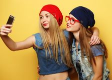 Happy girls  with smartphone  over yellow background. Happy self Royalty Free Stock Image