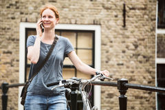 Lifestyle - Woman with Bicycle on the Phone Stock Images