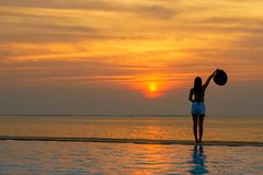 Lifestyle woman happy in big hat relaxing and freedom on the swimming pool near the sea and beach in the sunset, stock images