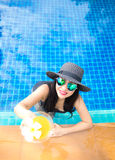 Lifestyle Woman in swimsuit relaxing and happy with cocktail on chaise-longue near swimming pool, summer day, select focus. Stock Photos
