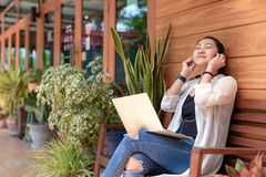 Lifestyle women freelance enjoy listening music and play laptop outdoors work space in the coffee shop for working . Lifestyle woman freelance enjoy listening royalty free stock photography
