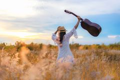 Lifestyle women white dress holding a guitar on a cloudy sunset or sunrise sky in the meadow flower, relax and happy day on summer stock photo