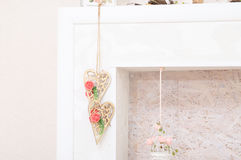 Lifestyle with wooden hearts with white and pink flowers in fireplace for lush interior. home decor. country house decor Royalty Free Stock Photography