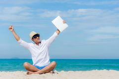 Lifestyle young asian man relaxing after working on laptop while sitting on the beautiful beach, freelance working on holiday summ royalty free stock photography