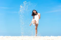 Lifestyle young asian woman relax kick sand and jumping on the beautiful beach. On holiday summer, blue sky background. Summer Concept stock photography