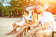 Young people enjoying summer vacation sunbathing drinking at beach bar Stock Image
