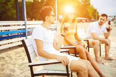 Young people enjoying summer vacation sunbathing drinking at beach bar Stock Photography