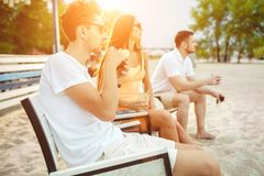 Young people enjoying summer vacation sunbathing drinking at beach bar Royalty Free Stock Photos