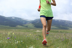 Lifestyle young woman runner running on beautiful trail in grassland Stock Photo