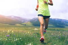 Lifestyle young woman runner running on beautiful trail in grassland Stock Image