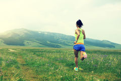 Lifestyle young woman runner running on beautiful trail in grassland Royalty Free Stock Photos