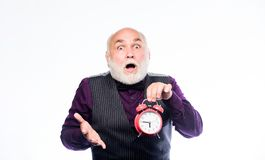 Lifetime ageing and getting older. Time does not spare anyone. Time and age concept. Bearded man clock ticking. Aged man. Holding alarm clock. Senior man white royalty free stock photo