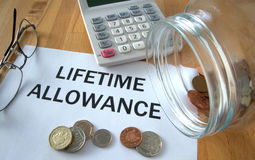 Lifetime allowance. Primary protection with coins on paper and in pot and calculator behind Royalty Free Stock Photography