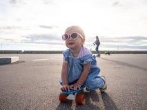 Lifstyle射击:桃红色太阳镜和一件蓝色礼服的一个愉快的小女孩坐冰鞋板 免版税库存图片