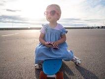 Lifstyle射击:桃红色太阳镜和一件蓝色礼服的一个愉快的小女孩坐冰鞋板 免版税库存照片