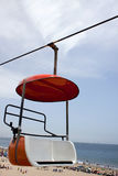 Lift on the Beach. An empty sky bench seat lift hanging from a wire on a clear day at the beach Stock Image