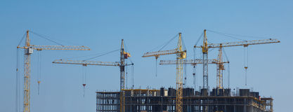 Lift cranes building a new residential building on blue sky back Stock Image