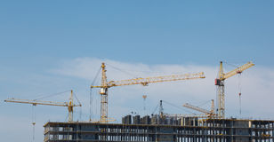 Lift cranes building a new residential building on blue sky back Royalty Free Stock Photos