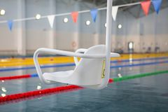 Lift for the descent of people with disabilities into the pool. On a blurred background, a swimming pool is visible royalty free stock photos