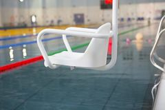 Lift for the descent of people with disabilities into the pool. On a blurred background, a swimming pool is visible royalty free stock image
