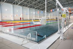 Lift for the descent of people with disabilities into the pool. On a blurred background, a swimming pool is visible stock photos