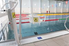 Lift for the descent of people with disabilities into the pool. On a blurred background, a swimming pool is visible stock photo