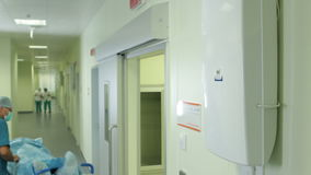 Lift door opens and doctor transports patient along hall stock footage