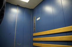 Lift inside 1. Inside of goods lift / freight elevator; blue painted; door closed; deserted royalty free stock photo