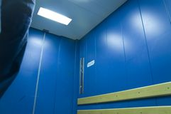 Lift inside 2. Inside of goods lift / freight elevator; blue painted; door closed; deserted stock photography
