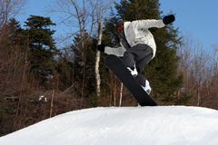 Lift off!. A snow boarder takes a jump at a mountain in New Hampshire Stock Photo