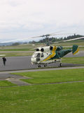 Lift Off. Airfield crew walking towards chopper Royalty Free Stock Photo