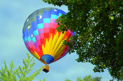 Lift Off. A multi-colored hot air balloon takes off for flight Royalty Free Stock Image