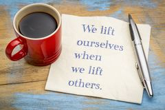 We lift ourselves by lifting others. Inspiraitonal handwriitng on napkin with a cup of coffee stock photos