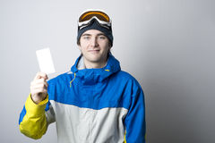 Lift pass with winter sports enthusiast. Young man holding blank ski lift pass looking. Concept to illustrate ski admission fee Stock Photos