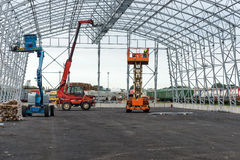 Lift with platform work in warehouse hangar construction field. Royalty Free Stock Photos