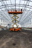 Lift with platform work in warehouse hangar construction field. Royalty Free Stock Photo