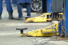 Lift`s arms in a car repair station. Yellow close up lift`s arms in a car repair station royalty free stock photography